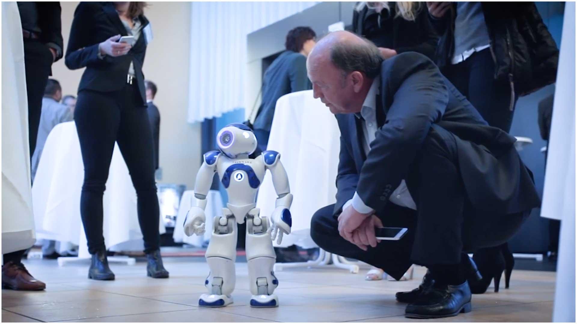 kambeckfilm_eventfilm2 Mann schaut sich Roboter an